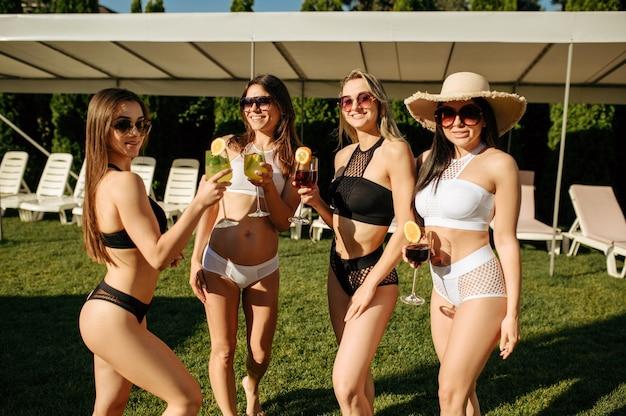 Donne sexy in costume da bagno posa con cocktail freschi, festa in piscina all'aperto. belle ragazze si rilassano a bordo piscina in una giornata di sole, vacanze estive di amiche attraenti