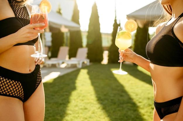 Donne sexy con cocktail freschi svaghi all'aperto. belle ragazze si rilassano a bordo piscina in una giornata di sole, vacanze estive di amiche attraenti