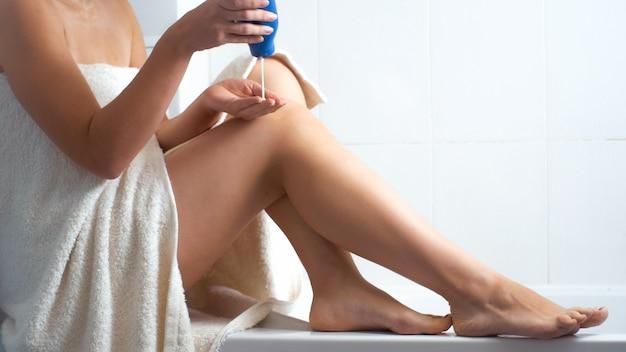Giovane donna sexy in asciugamano che applica lozione sulle gambe lunghe in bagno.