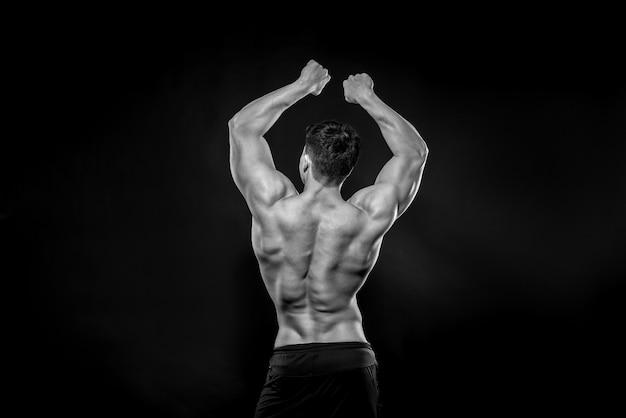 Giovane atleta sexy che propone su una priorità bassa nera nello studio. fitness, bodybuilding, bianco e nero