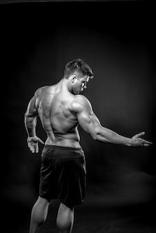 Giovane atleta sexy che propone su una priorità bassa nera nello studio. fitness, bodybuilding, bianco e nero.