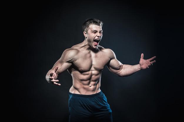 Giovane atleta sexy che propone su uno spazio nero. fitness, bodybuilding