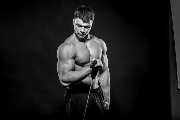 Giovane atleta sexy che posa su uno spazio nero nello studio. fitness, bodybuilding, bianco e nero.
