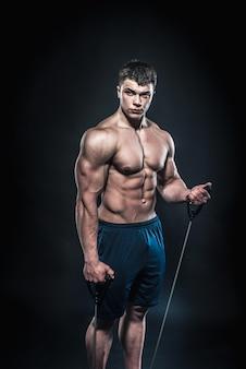 Giovane atleta sexy che posa su uno spazio nero nello studio. fitness, bodybuilding.