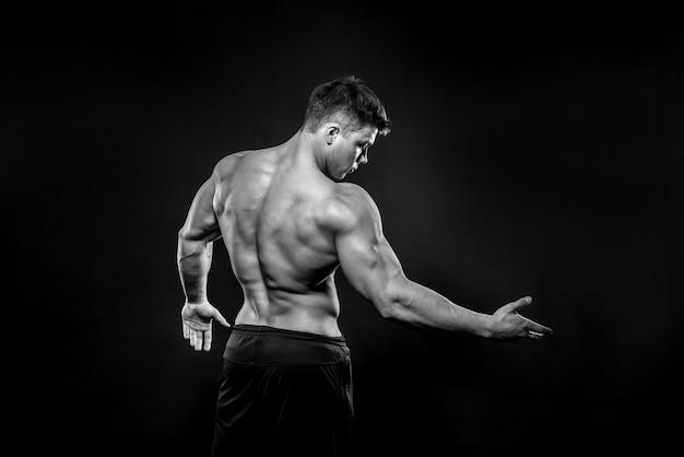 Giovane atleta sexy che posa sul nero nello studio. fitness, bodybuilding, bianco e nero.