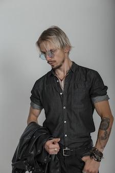 Giovane biondo sexy con tatuaggi in vestiti di jeans alla moda neri con una giacca in occhiali rotondi in posa in studio vicino a un muro vintage.