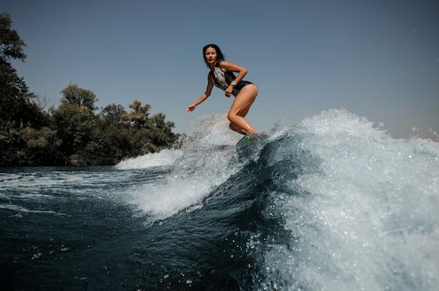 Giovane donna sexy del brunette che pratica il surfing a bordo giù l'acqua blu