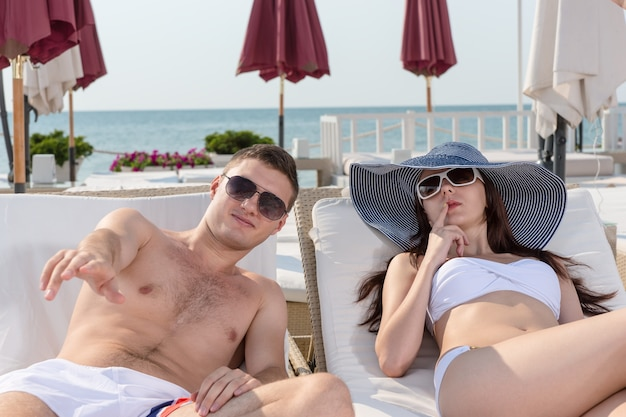 Sexy giovane coppia indossando occhiali da sole, rilassarsi sulle sedie a sdraio in un resort in un clima soleggiato.