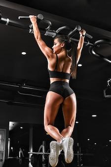 Ragazza sexy fitness giovane tira su nella donna fitness bruna palestra in abiti sportivi neri con corpo perfetto fitness in palestra, tirandosi sulla barra orizzontale