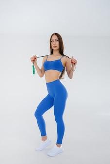 Ragazza sexy che salta la corda in una tuta blu su una superficie bianca