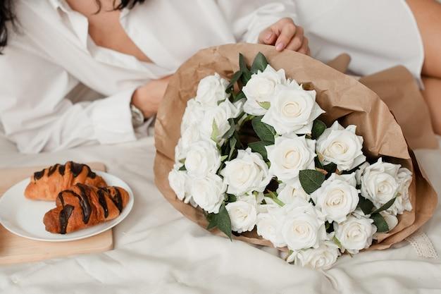 La ragazza sexy si trova in un letto bianco con fiori, un mazzo di rose l'8 marzo. un mazzo di fiori decorativi bianchi.