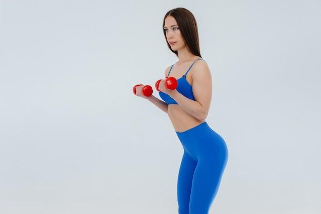 Ragazza sexy esegue esercizi sportivi su una superficie bianca