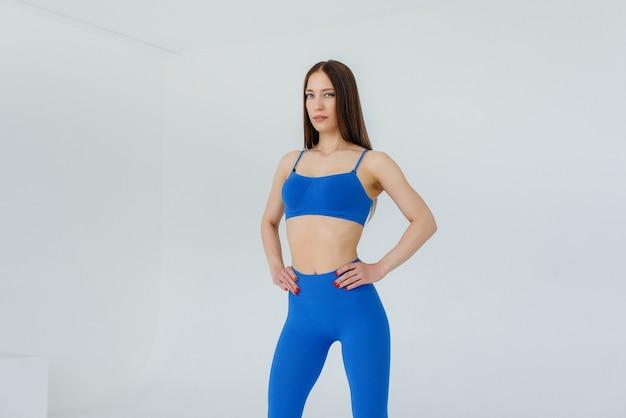 Ragazza sexy che posa in una tuta da ginnastica blu su una superficie bianca