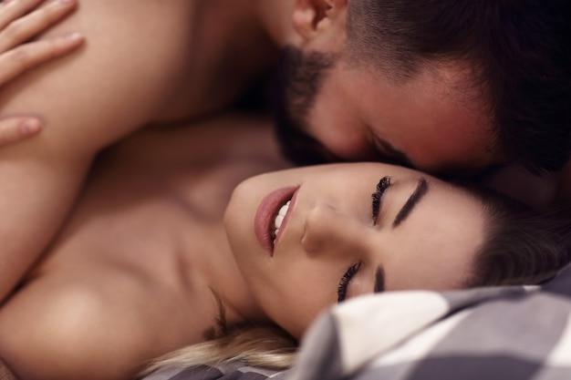 Giovani amanti sexy che sono intimi a letto