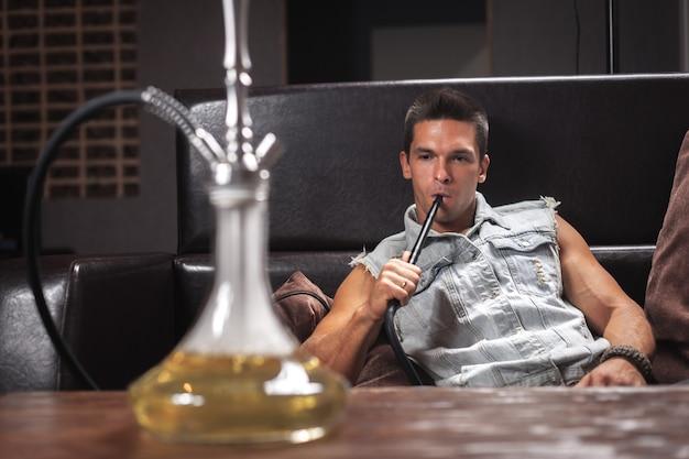 Giovane sexy che fuma un narghilè e problemi di fumo dalla bocca in discoteca.