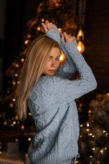 Giovane modella sexy di una bella donna bionda in un maglione lavorato a maglia alla moda in posa in una stanza buia contro un albero di natale festivo luminoso con ghirlande vintage