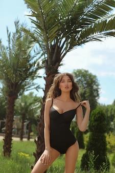 Sexy giovane modella con seno grande e vita sottile che regola il suo costume da bagno e guarda nella telecamera all'aperto vicino alle palme esotiche
