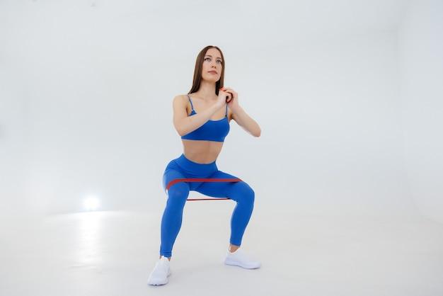 Sexy giovane sportiva esegue esercizi sportivi su un muro bianco