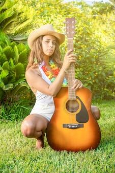 Sexy giovane donna dagli occhi dritti con la sua chitarra in un giardino