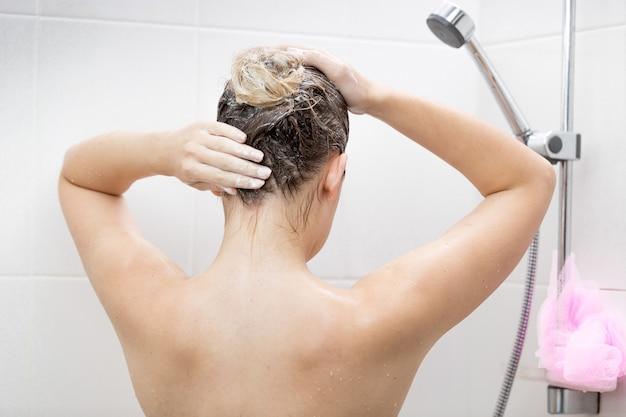 Giovane donna sexy che applica la lozione per capelli nella doccia