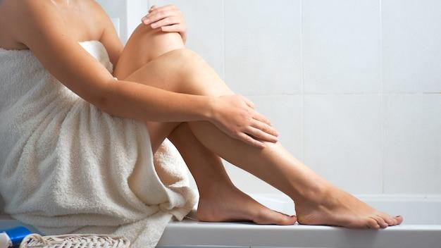 Giovane donna sexy in telo da bagno strofinando e massaggiando le gambe dopo aver fatto la doccia.