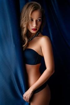 La giovane donna sexy in biancheria nera sta alla finestra avvolta in una tenda