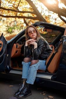 La giovane donna sexy in jeans è triste in una cabriolet