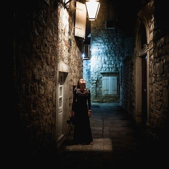 Giovane donna sexy in abito lungo nero in piedi sotto la lanterna nella vecchia strada stretta