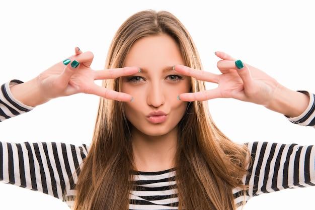 La giovane donna sexy osserva attraverso due segni di pace