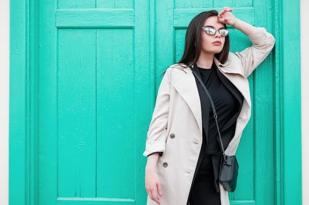 Giovane donna sexy in eleganti occhiali da sole retrò in t-shirt nera alla moda in trench primaverile alla moda è riposo vicino alla porta turchese in legno brillante vintage sulla strada. modello di ragazza attraente in città.