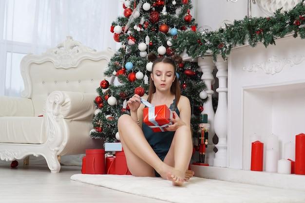 Giovane donna sexy in biancheria intima apre il contenitore di regalo vicino all'albero di natale - interno bianco