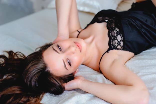 Sexy giovane donna in lingerie bianca si trova sul letto e abbraccia il cuscino. curve seducenti.