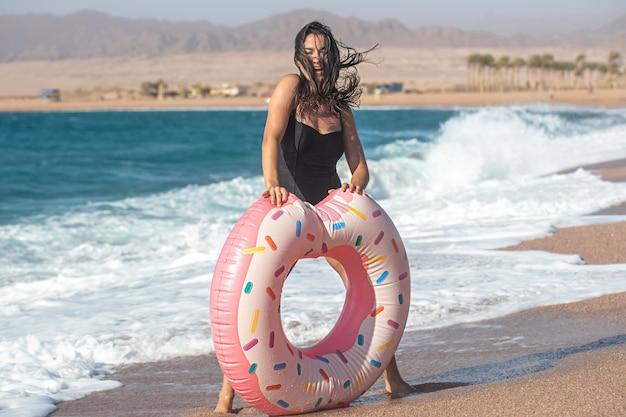 Una giovane donna sexy con un cerchio di nuoto a forma di ciambella in riva al mare. il concetto di svago e intrattenimento in vacanza.