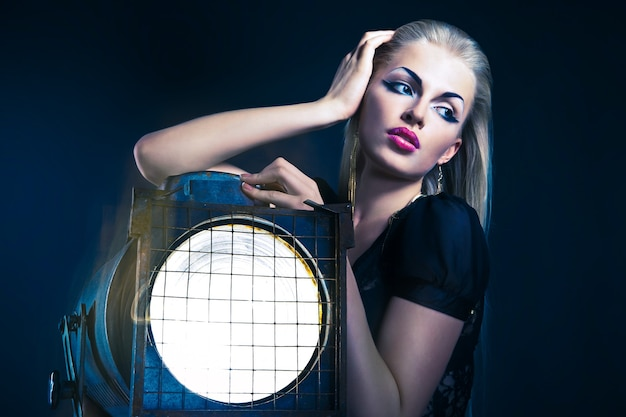Giovane donna sexy con un vecchio proiettore su sfondo scuro