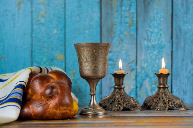 Candele di shabbat in candelieri di vetro pane challah sfocato