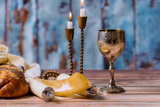 Tavolo della vigilia di shabbat, pane challah e candele