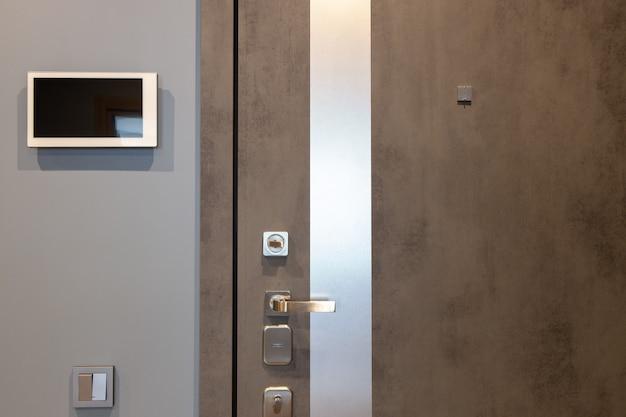 Porta d'ingresso dal design squallido nel corridoio di un appartamento moderno, dispositivo di videocitofono a parete. toni neutri.