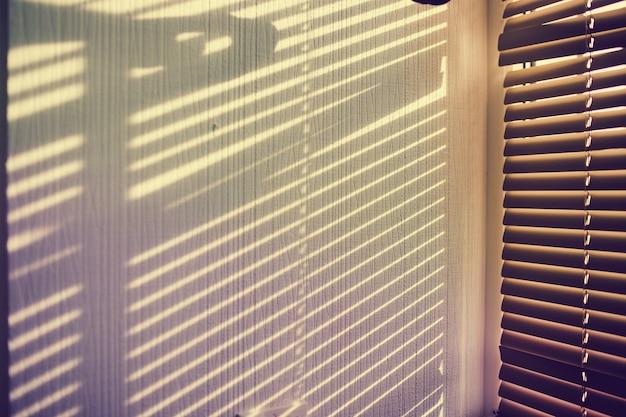 L'ombra della gelosia sul muro bianco.
