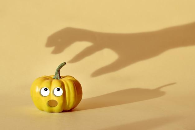 L'ombra della mano raggiunge la zucca con gli occhi. felice halloween. il minimo concetto di halloween.