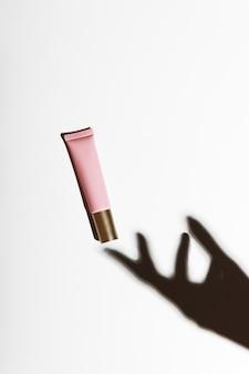 Ombra di una mano con un tubetto di crema rosa