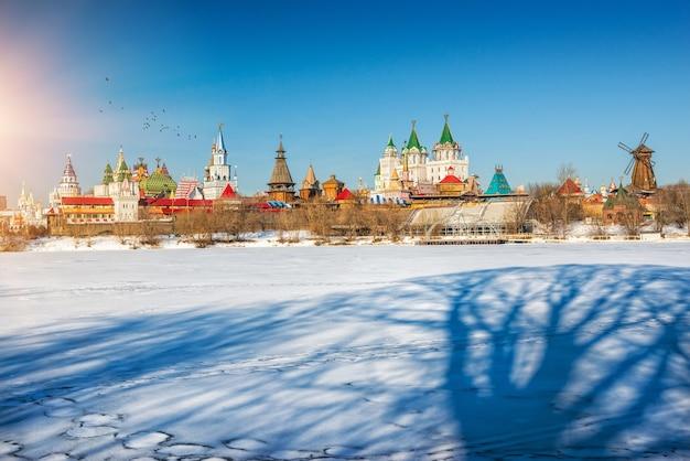 L'ombra di un grande albero nella neve vicino al cremlino di izmailovo a mosca una giornata di sole invernale