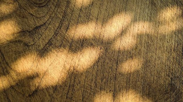 L'ombra delle foglie sovrapposizione naturale della luce solare sul vecchio fondo di struttura di legno