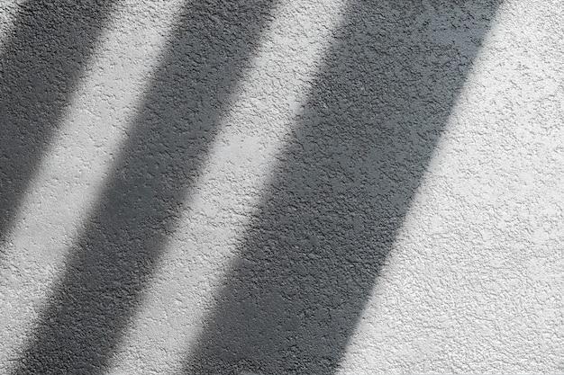 Ombra e luce attraverso le persiane finestra sul muro piastrellato luce mattutina e ombra sul muro