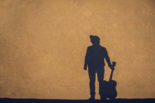 Ombra e silhouette del musicista con un cappello con una chitarra sullo sfondo di un muro di cemento