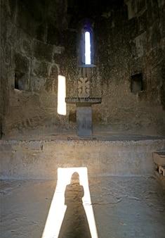 Ombra di una donna che indossa un copricapo che riflette sul pavimento di una vecchia chiesa di pietra