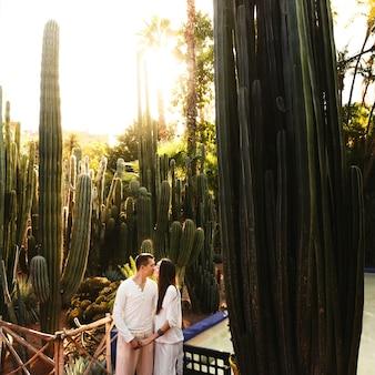 Le ombre nascondono le belle coppie che camminano in un giardino botanico africano