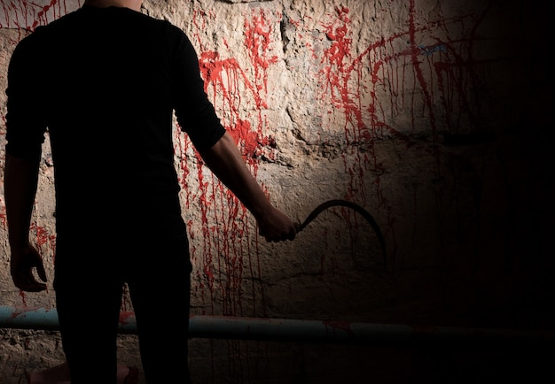 Figura maschile ombrosa che tiene la lama vicino al muro macchiato di sangue per il concetto di omicidio e spaventose vacanze di halloween