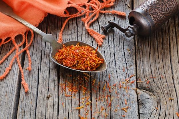 Shafran in un cucchiaio sul tavolo di legno con un panno di seta