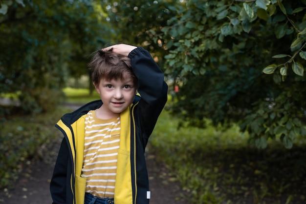Un bambino irsuto sta perplesso su uno sfondo di cespugli verdi