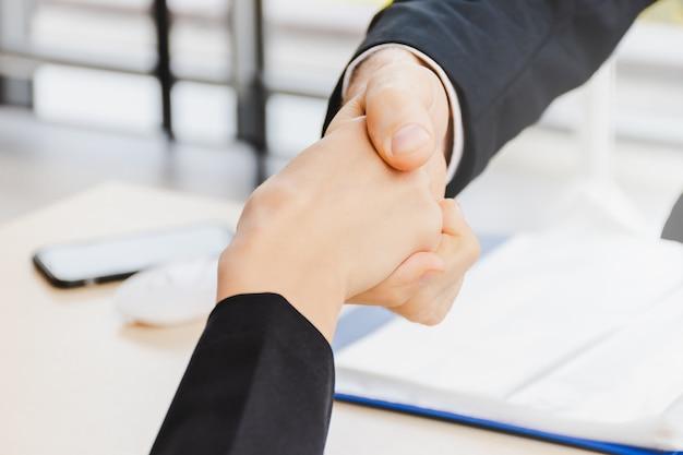 Stringe la mano di uomini d'affari tra uomo e donna in ufficio per il lavoro di squadra collaborativo.